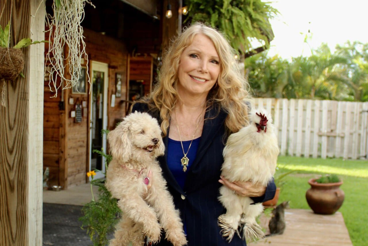 Image of Susan Hargreaves with her dog Lovey and a chicken